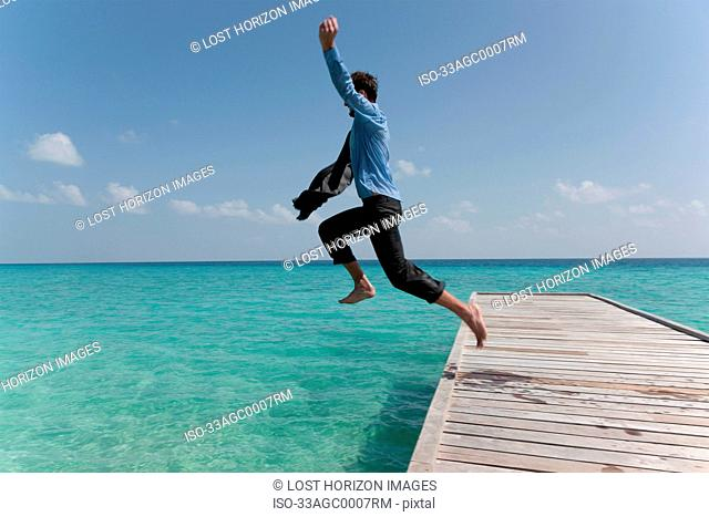 Businessman jumping from jetty into sea