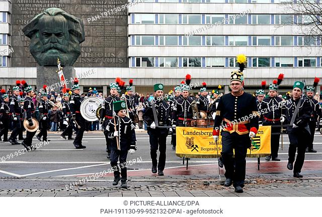 30 November 2019, Saxony, Chemnitz: Miners' associations pass by the Karl Marx Monument during the great mountain parade of the Erzgebirgische...