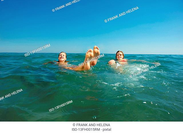 Two girls floating in the sea