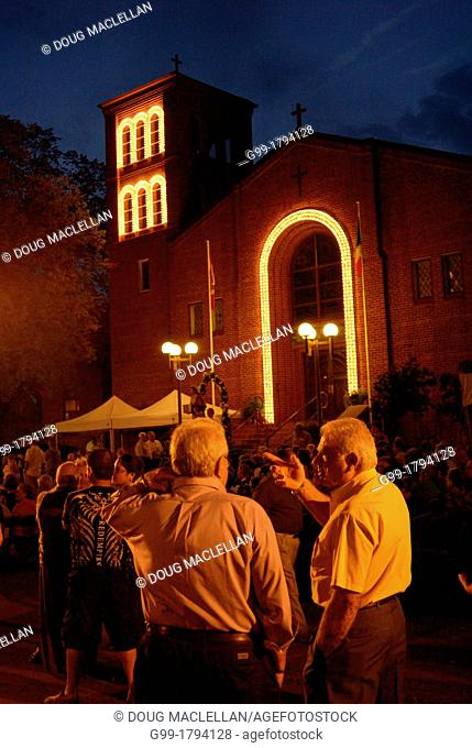 Two men talk in the late evening during St Angela Merici Church 25th Anniversary celebration weekend. The church is in the heart of Little Italy