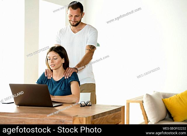 Woman working on laptop while boyfriend massaging her neck at home