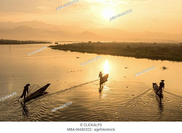 Inle lake, Nyaungshwe township, Taunggyi district, Myanmar (Burma). Three local fishermen in silhouette at sunrise