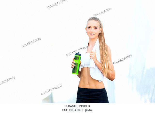 Portrait of young female runner in city holding water bottle