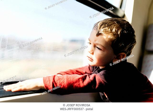 Portrait of little boy on his first train ride looking through window