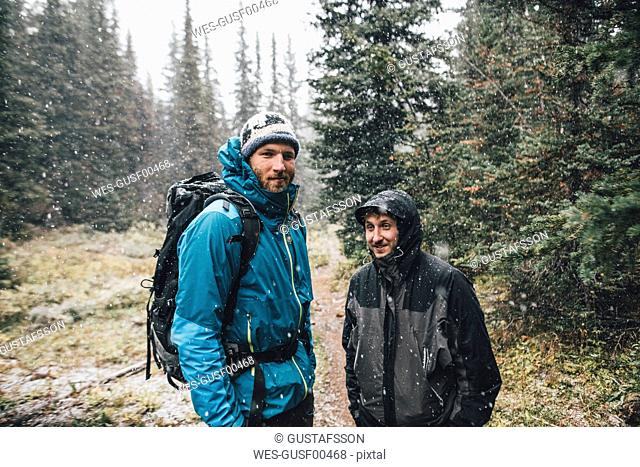 Canada, British Columbia, Yoho National Park, portrait of two smiling hikers in snowfall