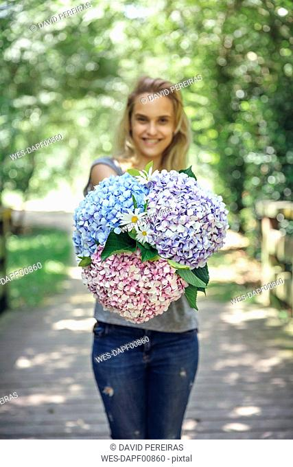 Smiling young woman showing a bouquet of hydrangeas and daisies