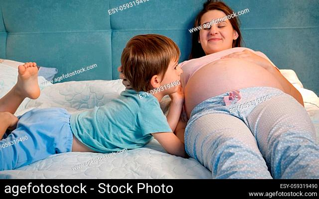 Portrait of little toddler boy in pajamas lying with pregnant mother in bed and talking to unborn baby in big belly. Loving and caring children