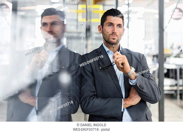 Businessman leaning against glass pane in modern factory thinking