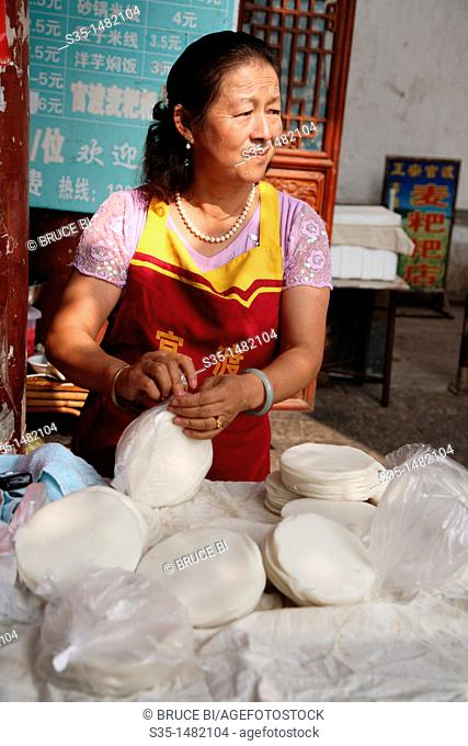 A lady selling home made Er Kuai Rice Cake on the main street  Town of Guandu  Kunming  China