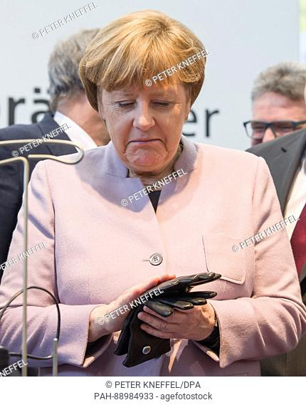 German Chancellor Angela Merkel looks at a stand for traditional glove manufacturing at the Handwerksmesse (Skilled Trade Fair) in Munich, Germany