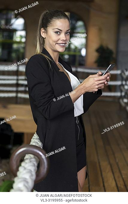Side view of elegant modern businesswoman in jacket standing indoors with smartphone in hands smiling at camera