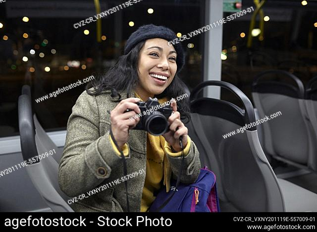 smiling woman taking photos in a public transportation