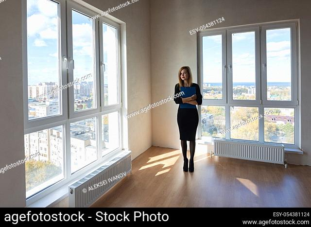 The girl with the folder stands in the middle of a large spacious room with large windows