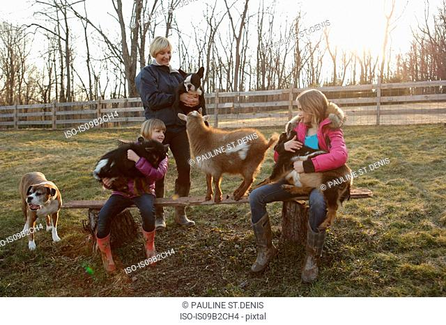 Mother and daughters outdoors, hugging goats and pet dog