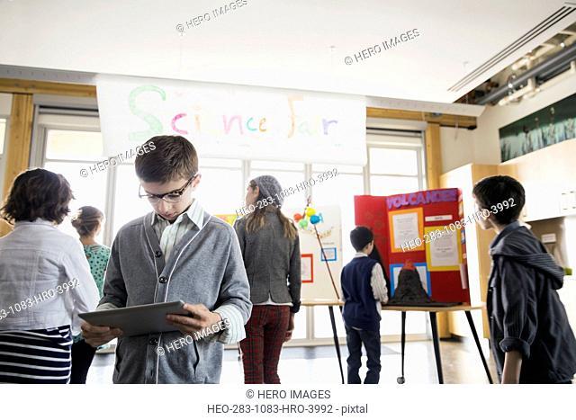 School boy using digital tablet at science fair