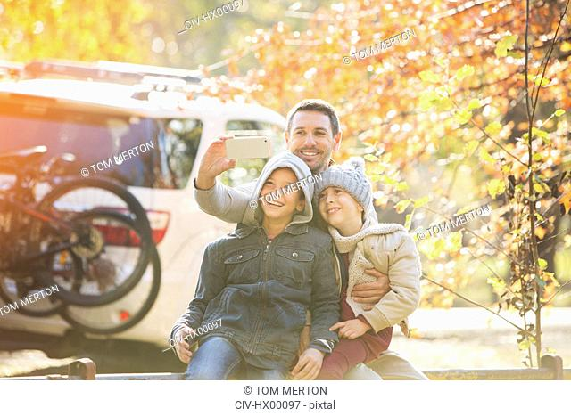 Father and sons taking selfie in autumn park