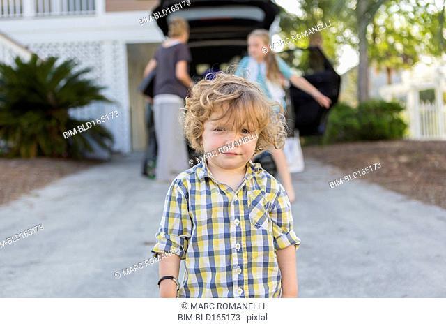 Caucasian baby boy standing in driveway