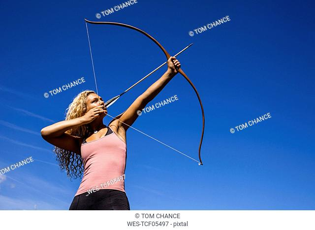 Archeress aiming with bow against blue sky