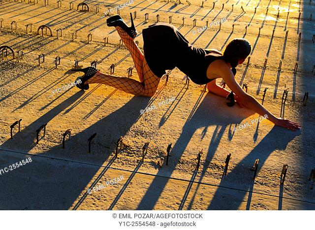 Pretty teen girl crawling before low sunset light