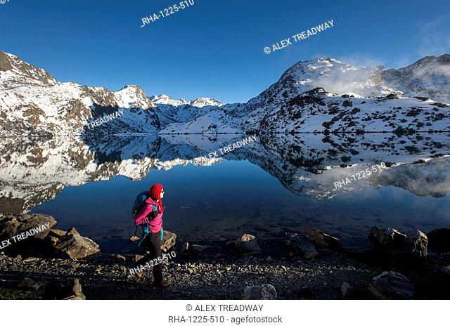 A woman walks past the holy lake of Gosainkund in the Langtang region, Himalayas, Nepal, Asia