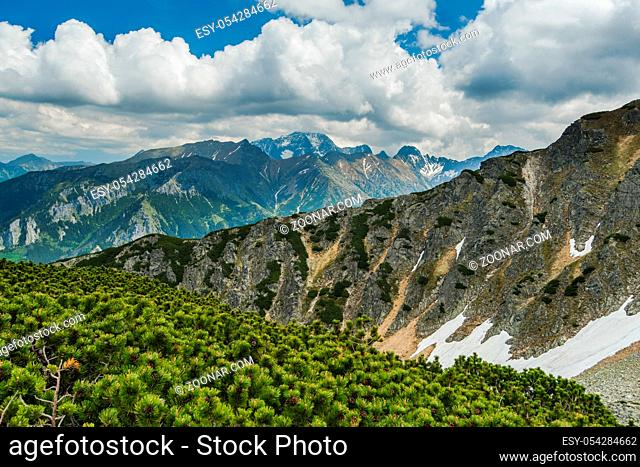 High mountains peaks in Tatra mountains, Poland. Clouds, sunnshine and snow patches