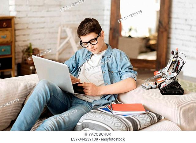 Keep silent please. Smiling boy holding laptop on the knees looking at copybook while making some notes