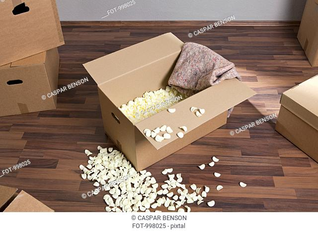 Moving boxes, packing peanuts and a drop cloth