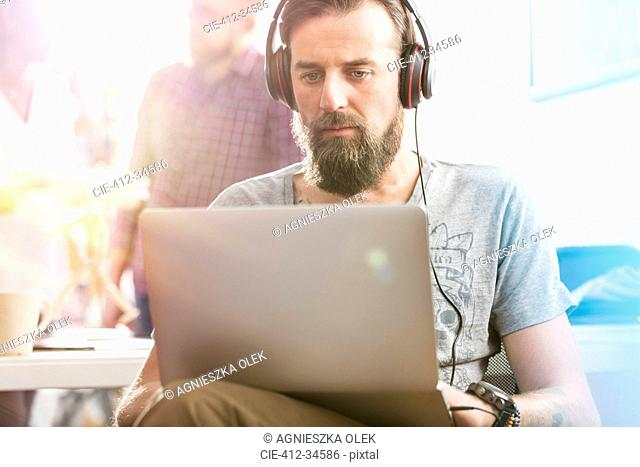 Serious male design professional with headphones using laptop in office