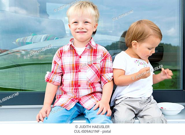 Boy and female toddler on patio eating bowl of raspberries