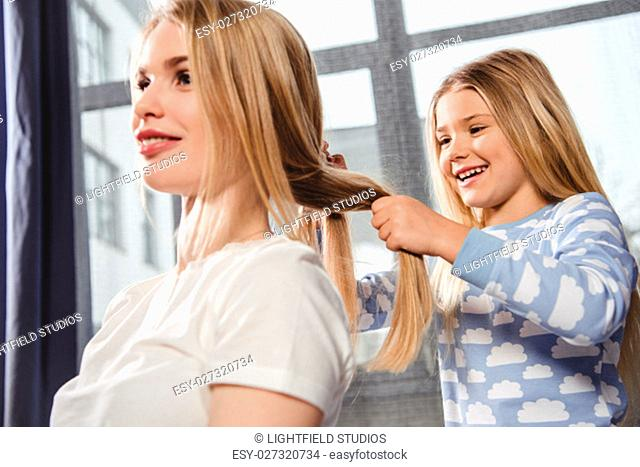 Cute smiling daughter in pajamas plaiting braid of mother