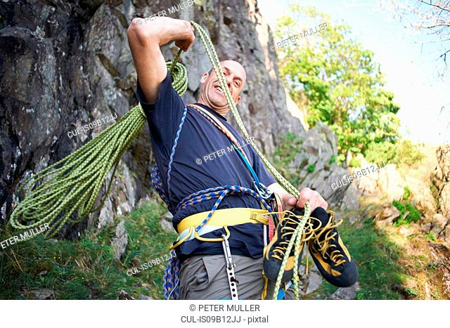 Rock climber preparing climbing ropes smiling