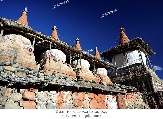 Mani wall (stones inscribed with a buddhist mantra) and stupa (chorten) in the village of Tangge. Nepal, Gandaki, Upper Mustang (near the border with Tibet)