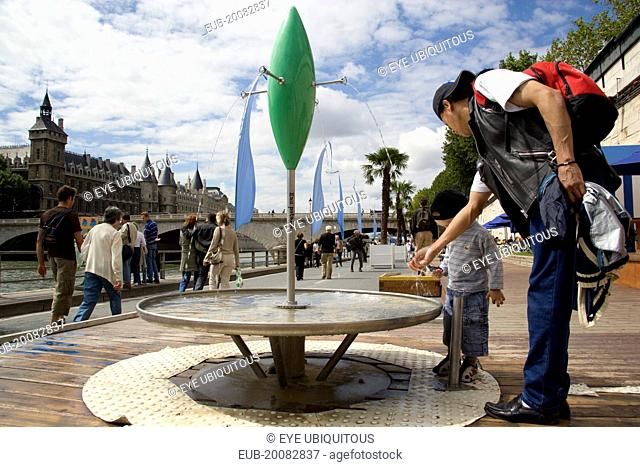 The Paris Plage urban beach. A small boy with an adult at one of the many free drinking water fountains on the Voie Georges Pompidou