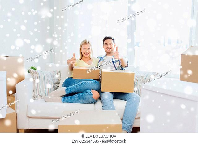 moving, people, repair and real estate concept - happy couple with cardboard boxes showing thumbs up on sofa at new home over snow