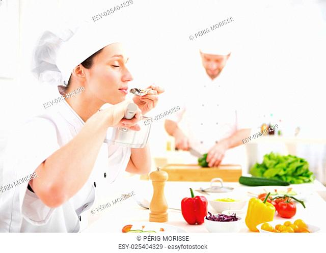 View of a Young attractive professional chef tasting sauce
