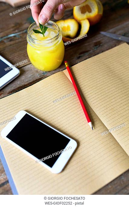 Glass of orange juice, notepad, pencil and cell phone
