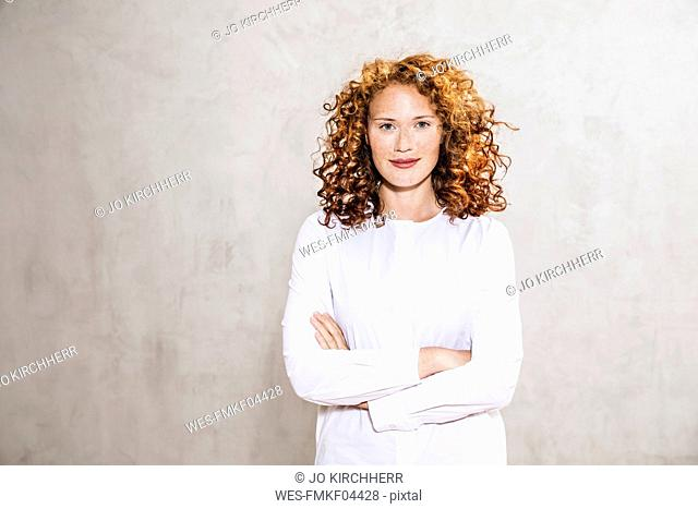 Portrait of redheaded young woman with arms crossed