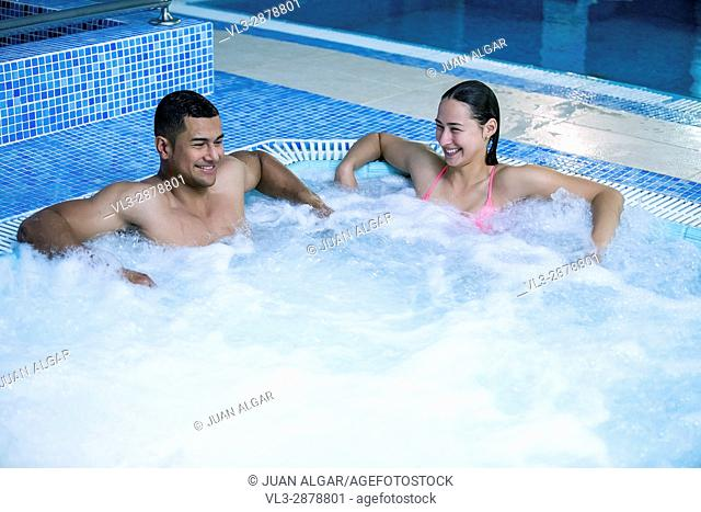 Horizontal indoors shot of man and woman having fun and relaxing in swimming pool with bubbles