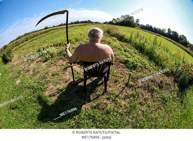 Farmer with a scythe sitting in the meadow. Landscape with old farmer sitting in green meadow. Farmer, meadow and blue sky