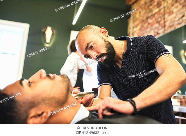 Focused male barber giving customer a shave in barbershop