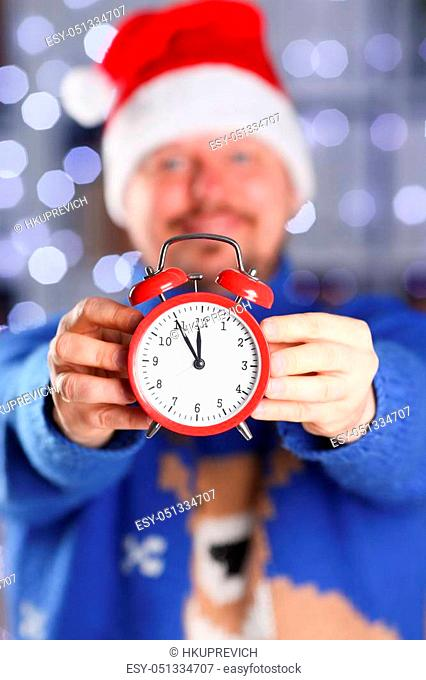 Bearded smiling man wearing warm blue sweater with traditional deer hold arm red alarm clock within inch coming 2018 year with glowing garland background...