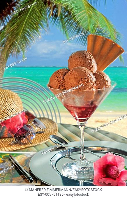 An ice cream sundae with chocolate ice cream filled before backdrop of tropical beach