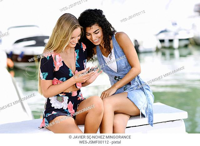 Two happy young women with cell phone at marina in summer