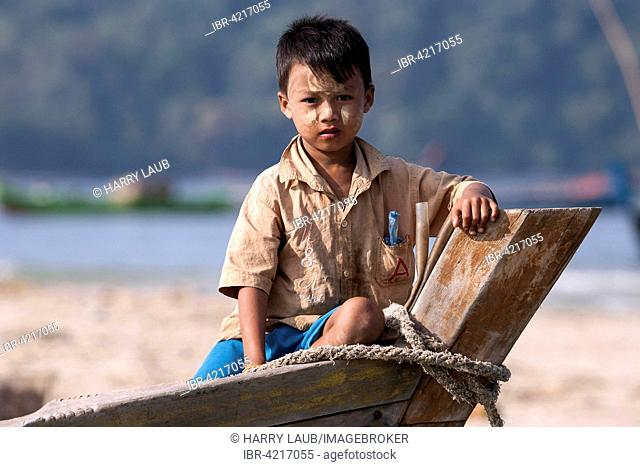Local boy with Thanaka paste on his face sitting on the bow of a fishing boat, fishing village of Ngapali, Thandwe, Rakhine State, Myanmar