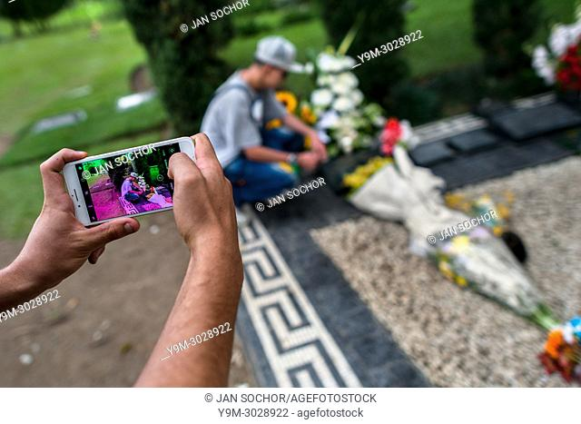 A young Colombian man takes a snapshot of his friend while visiting the tomb of the drug lord Pablo Escobar at the cemetery of Montesacro, in Itagüí, Colombia