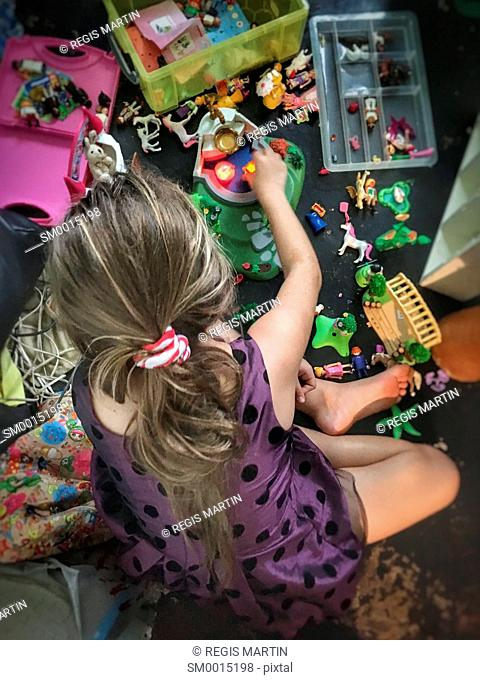 Young girl playing with her toys, view from above