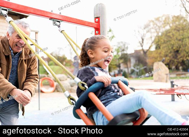 Playful grandfather pushing granddaughter on playground swing