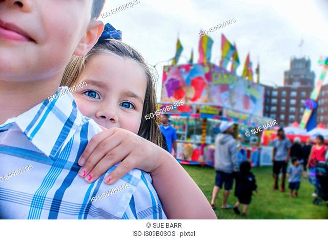 Portrait of cute girl peering from brothers shoulder at amusement park