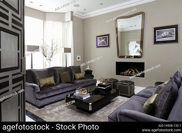 Door opening on to glamorous drawing room with purple velvet sofas and black and white photography | | Designer: Jordana Yechiel
