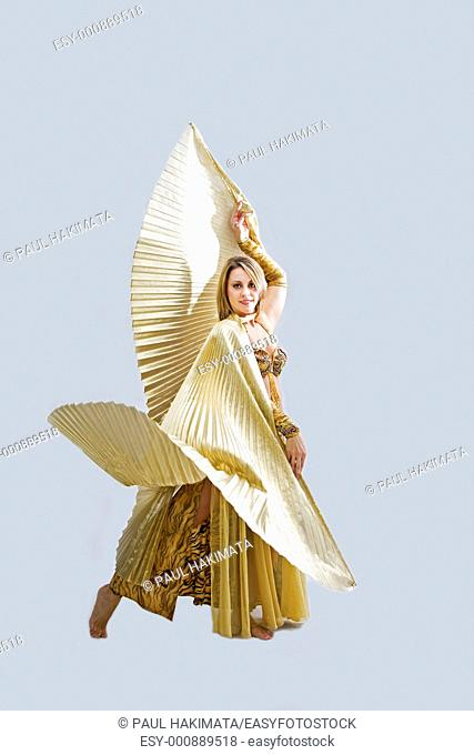 Beautiful belly dancer in gold outfit with wings, isolated